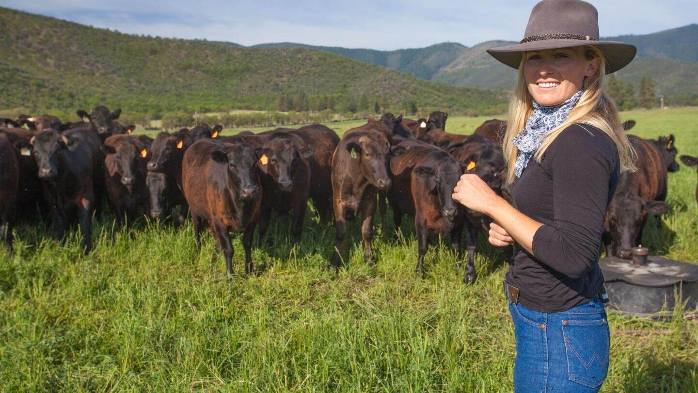 A woman wearing a cowboy hat smiles to the camera as a herd of cows are behind her.