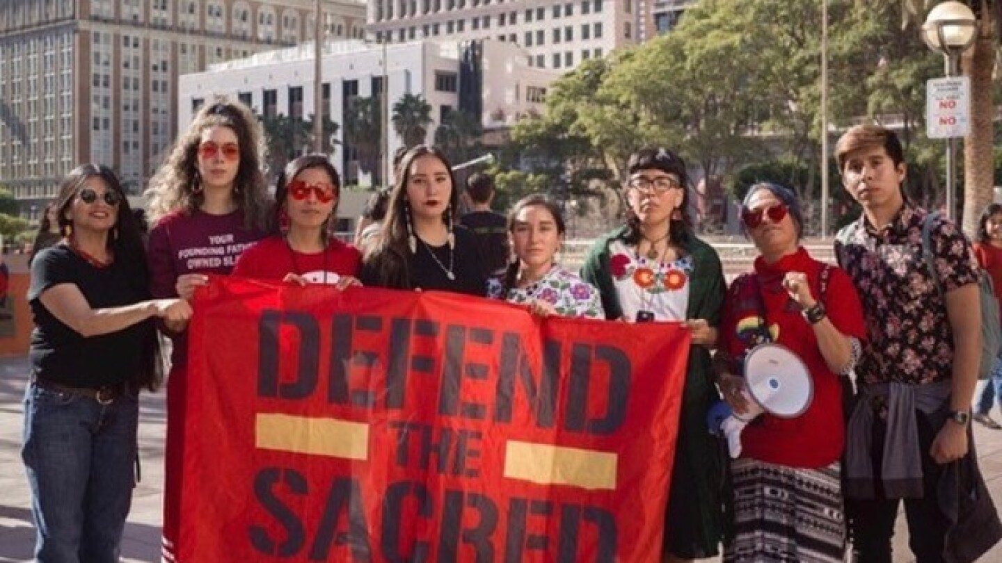 "The fourth person from the left, Bii Gallardo help hold a banner that reads ""DEFEND THE SACRED"" during the L.A. Women's March in January 2020."