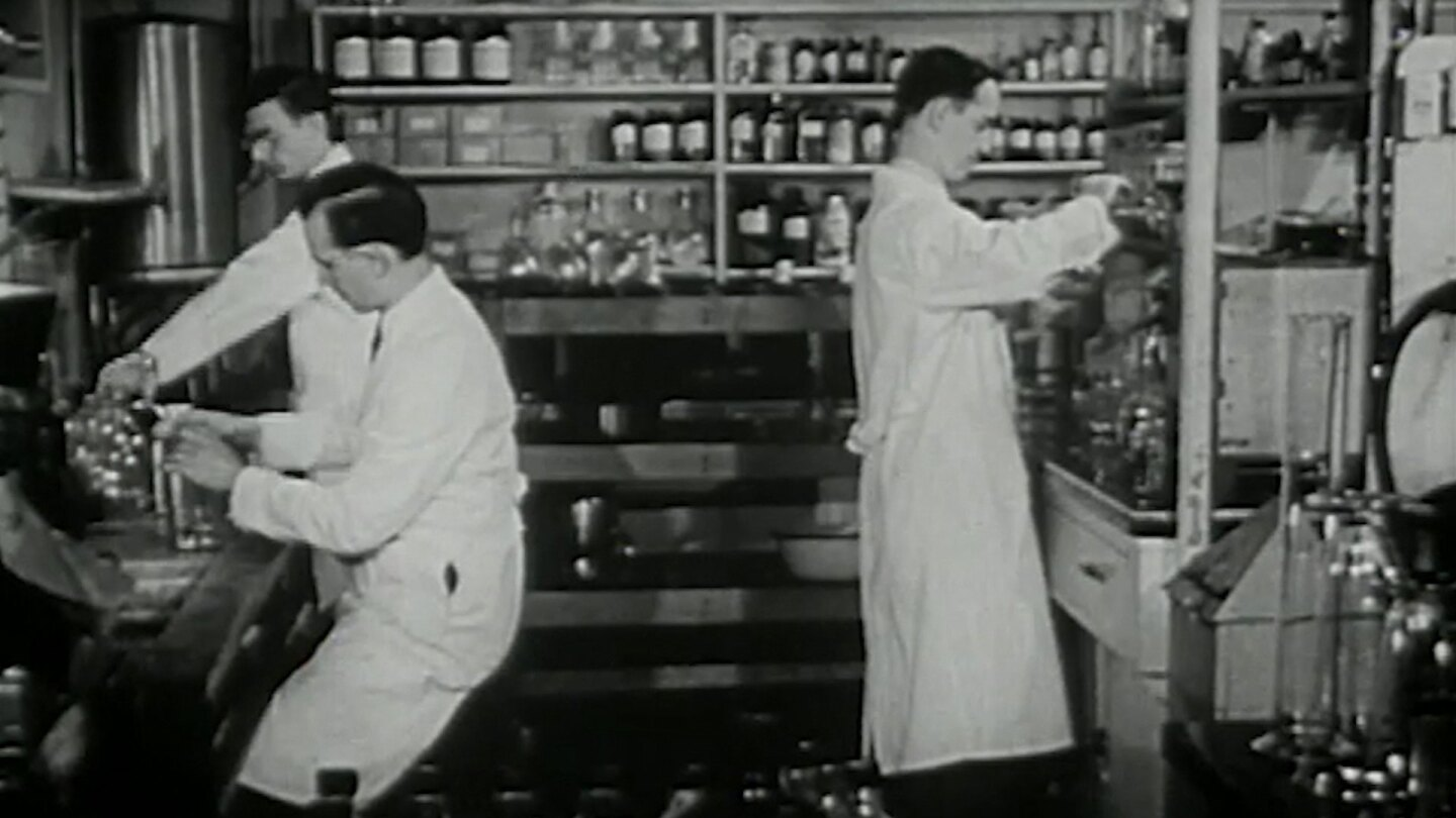 """Archival footage of scientists working in a lab. 