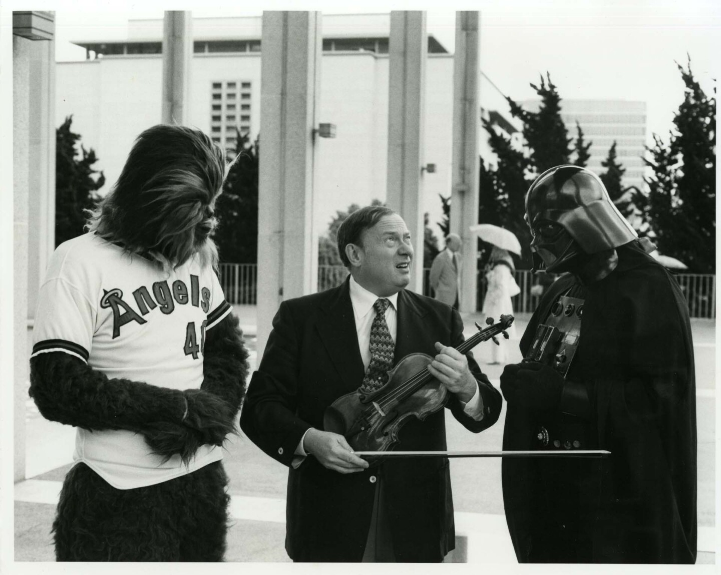 """Concertmaster Sidney Harth, Chewbacca in an Angels jersey and a costumed Darth Vader promote the Music from Outer Space concert at Anaheim Stadium after """"Star Wars"""" was released 