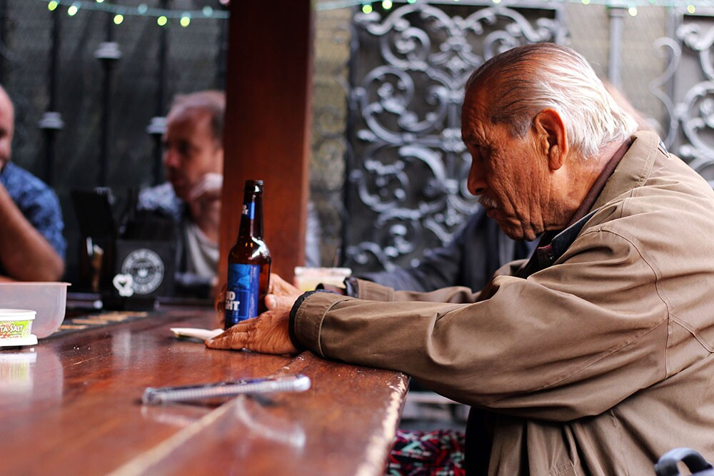 An older man sits at the La Cita bar with a Bud Light.