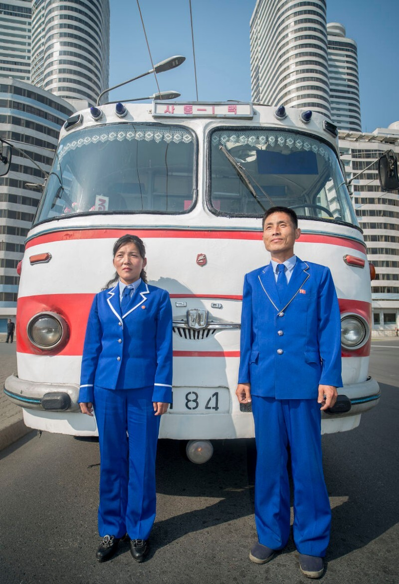 A bus driver and ticket taker stand in front of the historic bus that Kim Il Sung rode on. North Korea   Mark Edward Harris