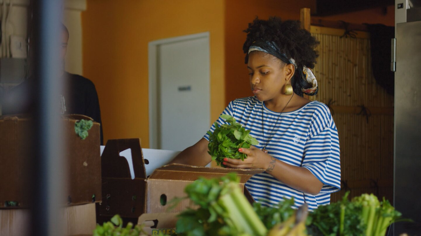 "Vegan grocer Olympia Auset assembles a box of fresh produce for a client. | Still from ""Broken Bread"""