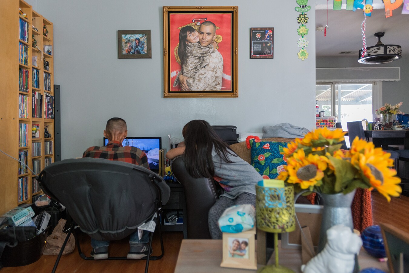 Rhianna watches her dad play a video game on a computer. Their backs are turned to the camera. In frame, you can see their home which is filled with sunflowers in a vase, photos of Rhianna and her dad, a shelf full of DVDs and vibrant throw pillows.