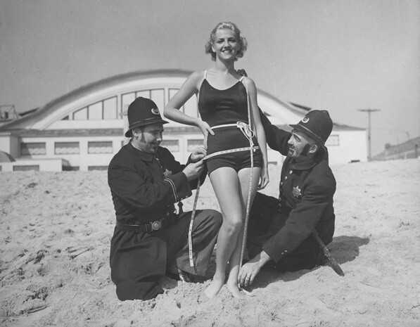Men in police costumes measure a woman in a bathing suit, circa 1920. From the Los Angeles Area Chamber of Commerce Collection.