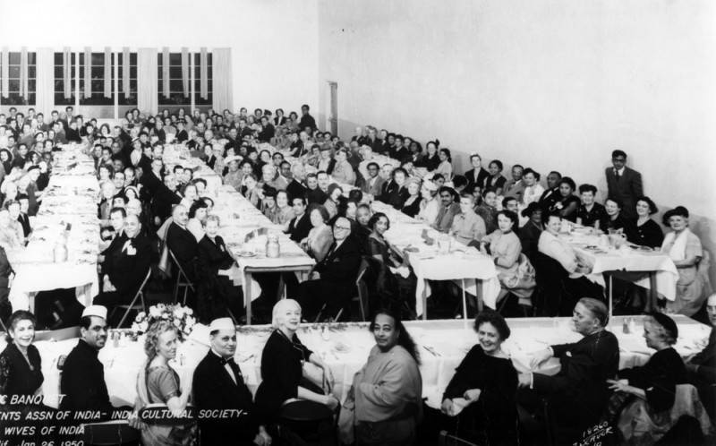 Black and white photo of a large group of people sitting at long tables