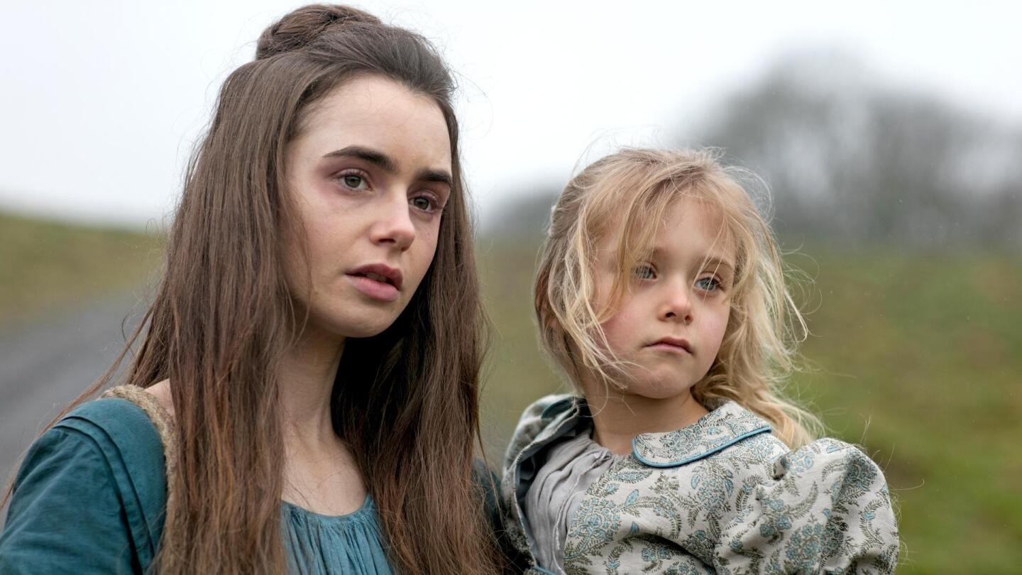 "Fantine (played by Lily Collins) holds her daughter Cosette. | Still from ""Les Miserables On Masterpiece"""
