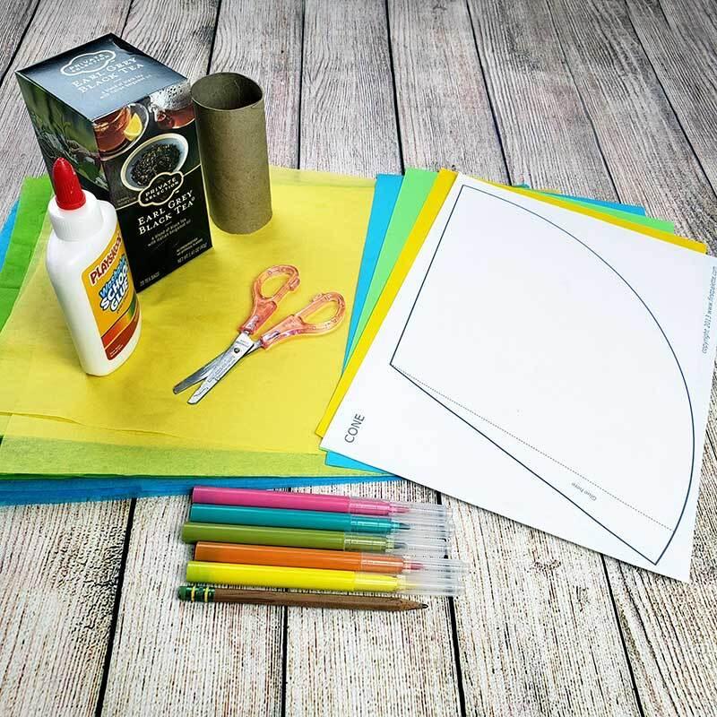 Materiales de manualidades, incluyendo papel de construcción, dos pequeñas cajas vacías, tijeras, pegamento y marcadores son colocados sobre una mesa.