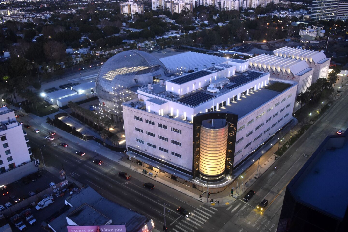 An aerial view of the Academy Museum of Motion Pictures is shot at night.
