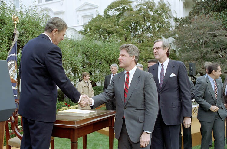 President Reagan shakes hands with Bill Clinton in the Rose Garden during signing ceremony for HR 1720 Welfare Reform Act of 1988, October 13, 1988.