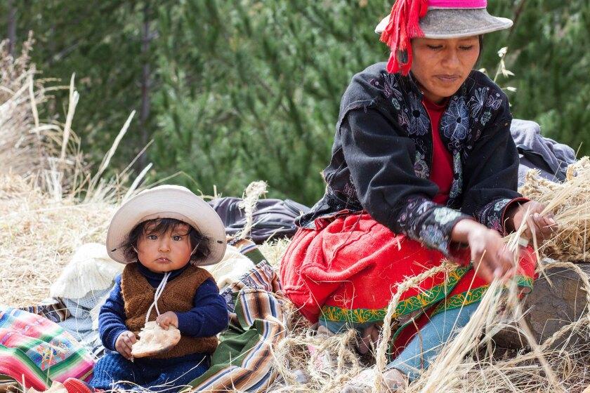 A baby plays alongside a woman braiding rope for the Q'eswachaka Bridge reconstruction.