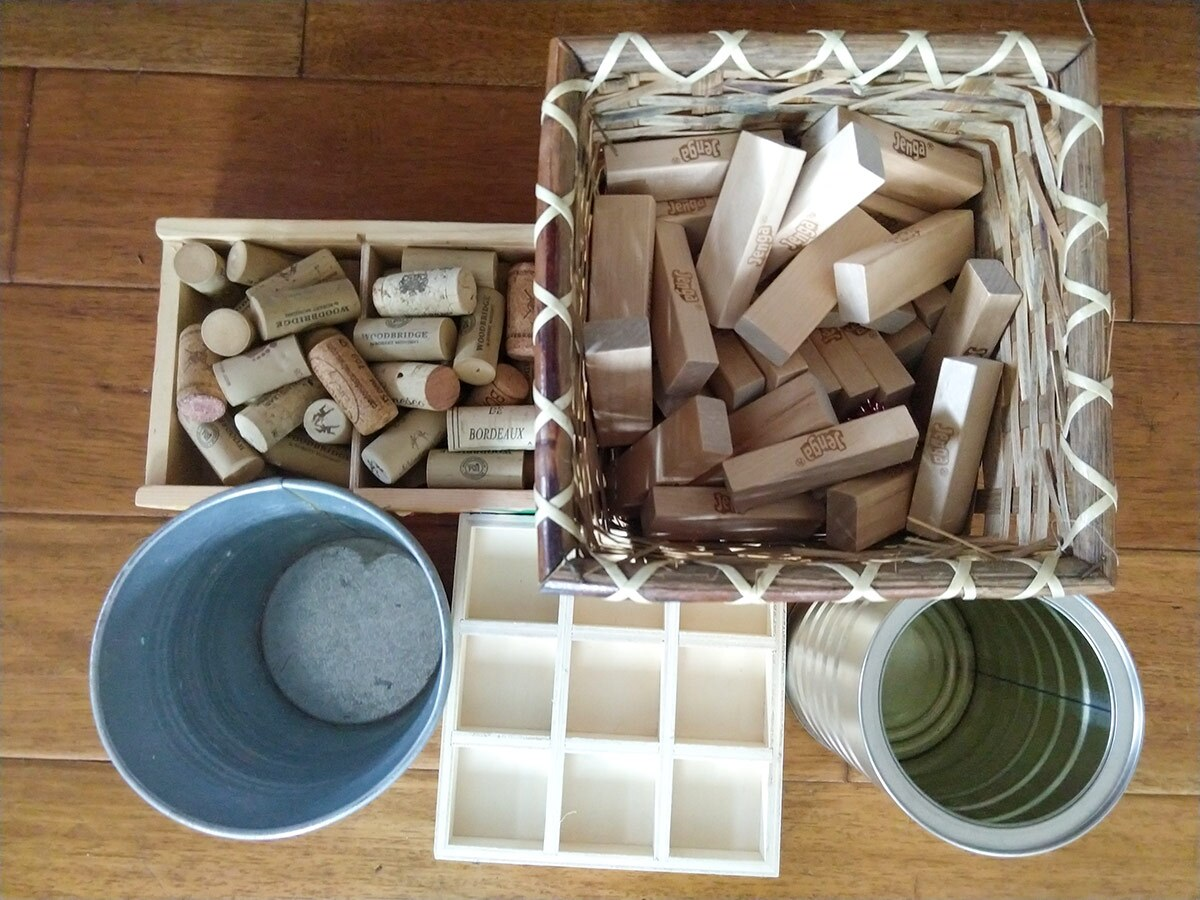Two small containers filled with small wooden blocks alongside two cups and an ice cube tray.