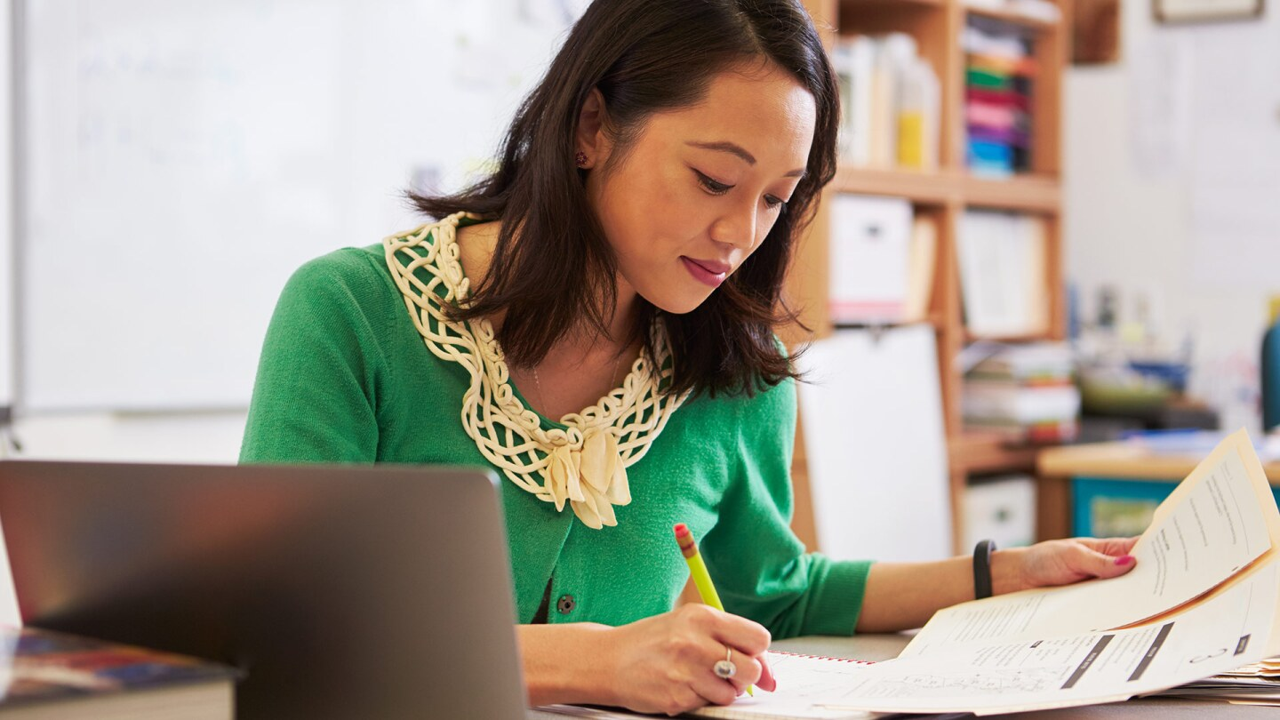 A woman in a green sweater looks down at some papers as she holds a pen. A laptop can be seen next to her. istock