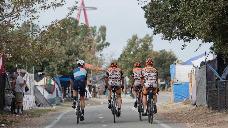 Bike riders pass through homeless camp