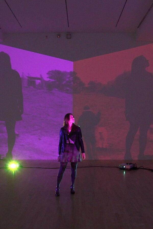 "A woman standing in a room with her silhouette projected on four different screens. | ""Art21: Los Angeles"""
