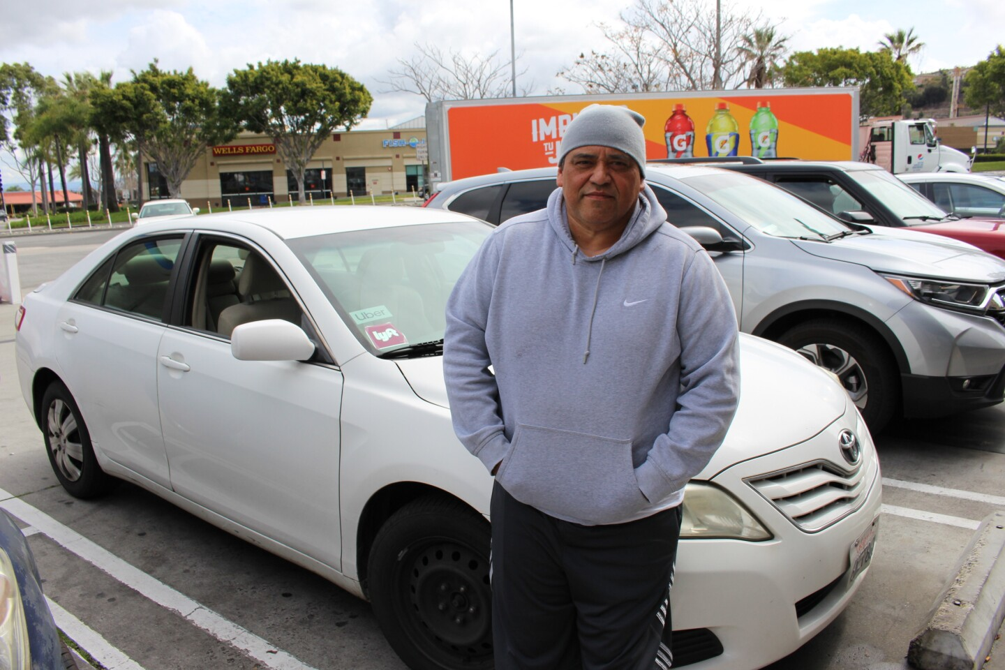 Ruben Gonzalez, uber driver, poses with his car