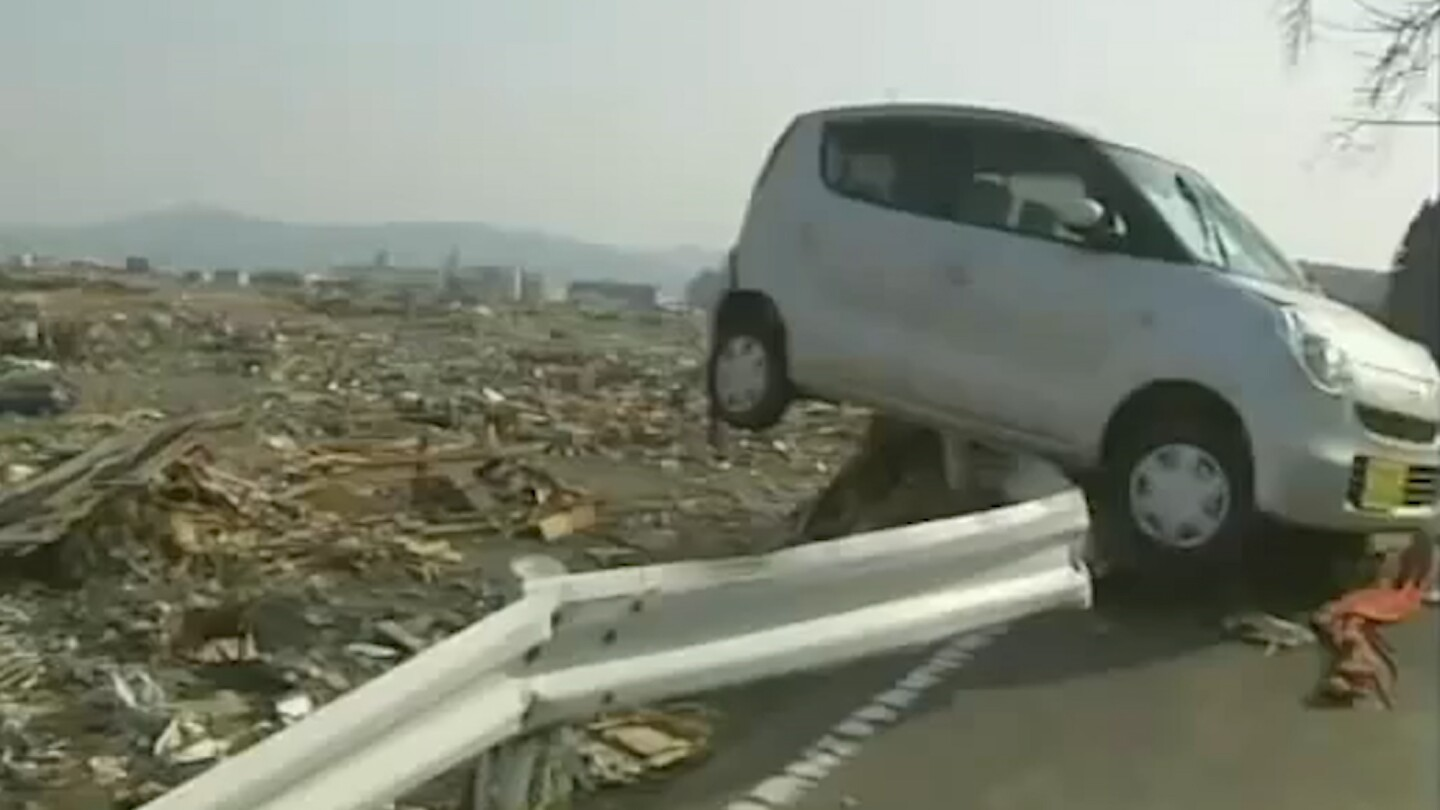 A car barely hangs over a railing in the aftermath of the 2011 Tohoku earthquake in Japan.