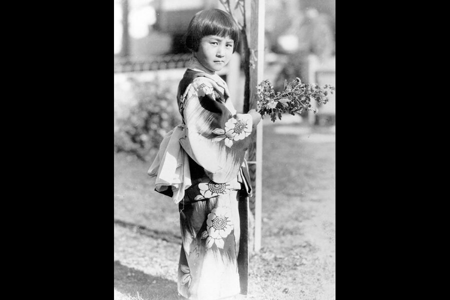 A Japanese American girl in a kimono holds a small bouquet, 1934