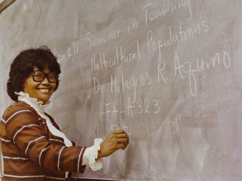 A woman writes on a blackboard