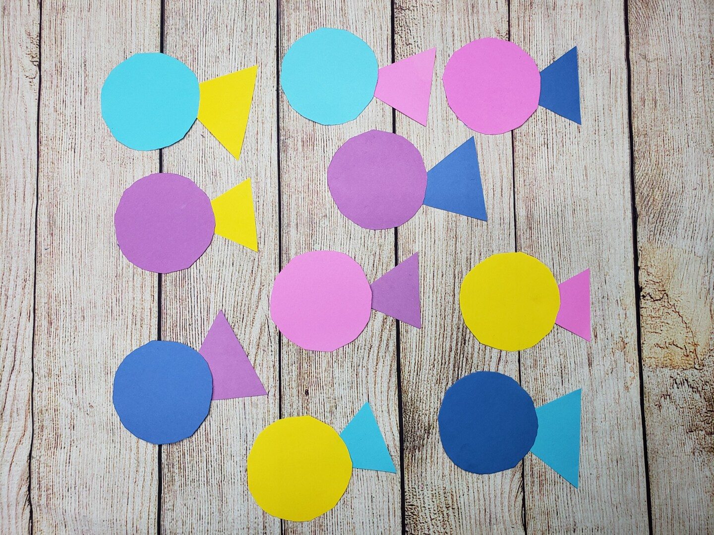 Ten colorful fish shapes made out of circles and triangles made out of construction paper.