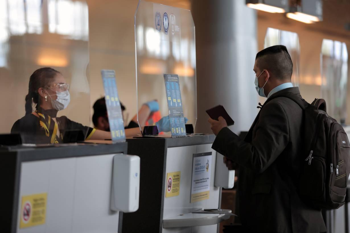An employee of Spirit airline wearing a face mask asks a passenger for a passport