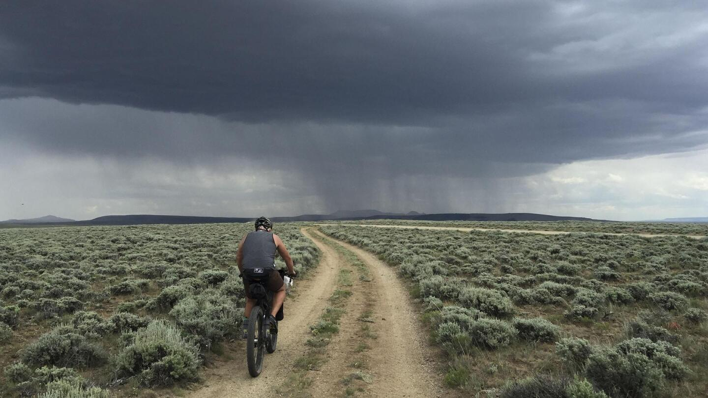 A bicyclist bikes on a dirt road on an ominously cloudy day.