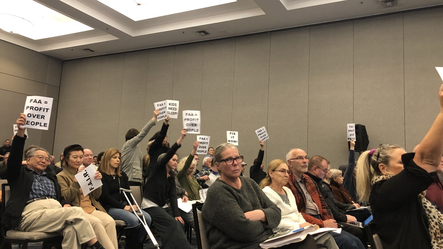 People holding signs against F.A.A while sitting in a meeting about Burbank Airport Noise