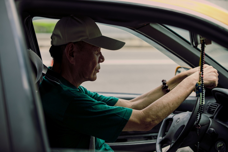"An elder taxi driver behind the wheel | Still from ""A-Tien"" Fine Cut season 21 preview"