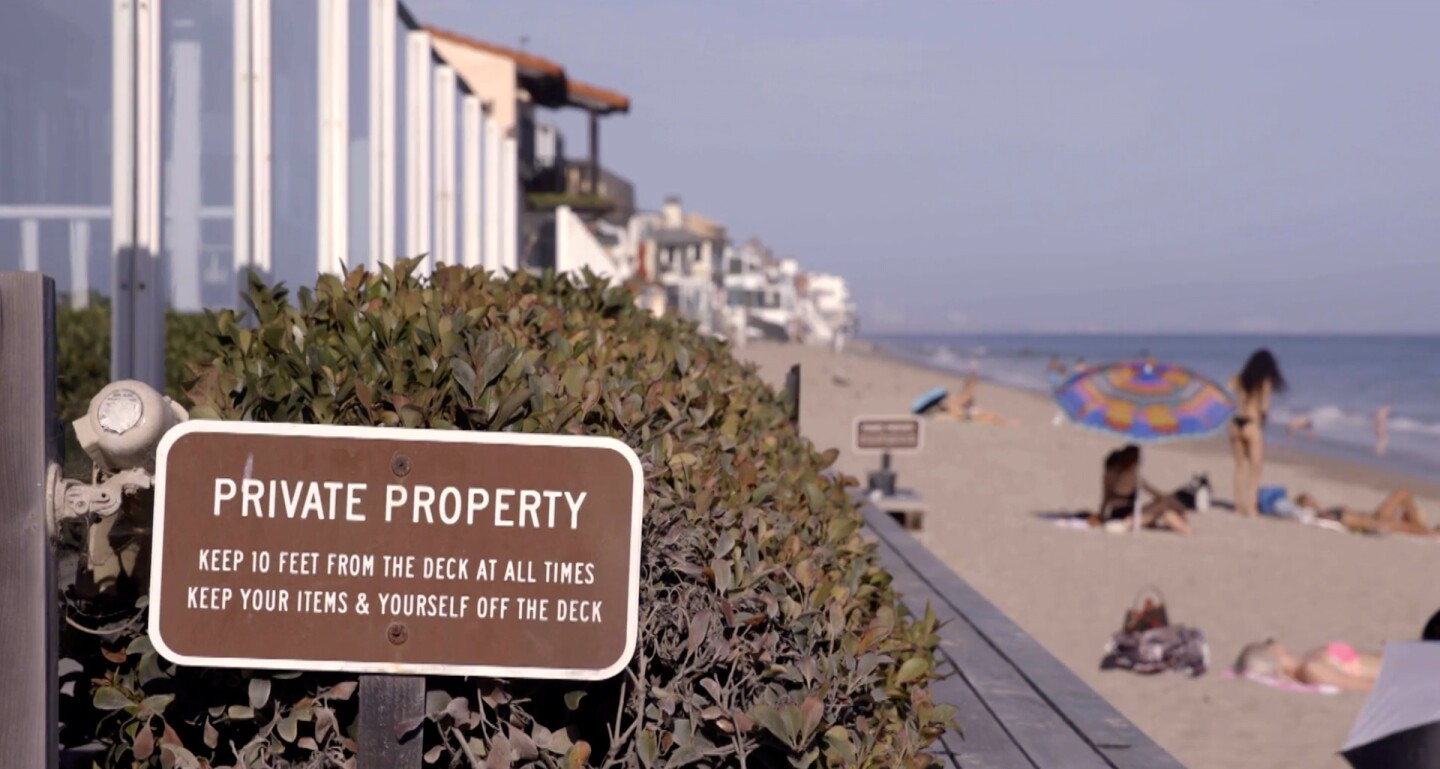 """Private Property sign in foreground with beach behind it 