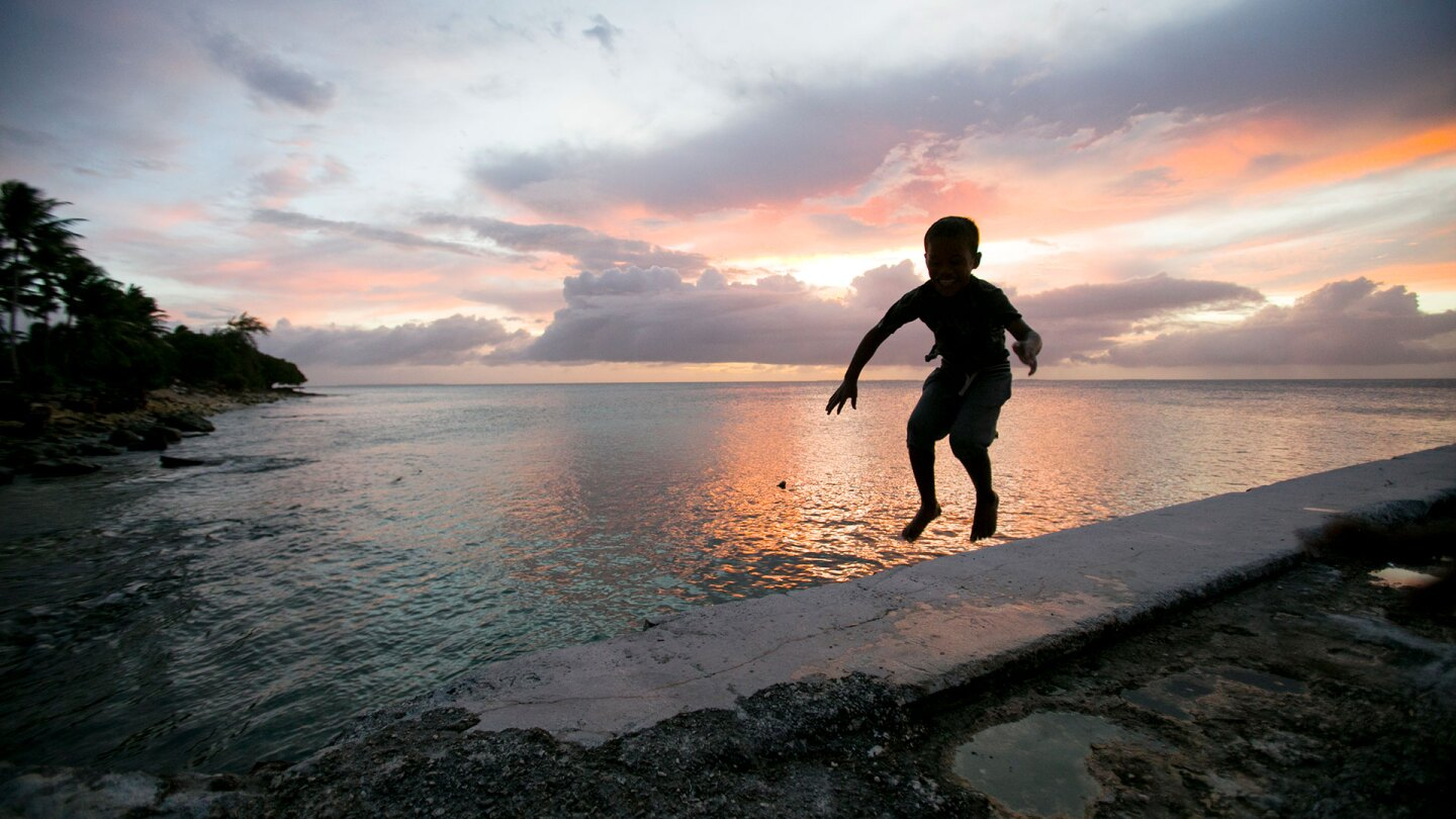 A little boy jumps near the ocean surrounding the Marshall Islands, which are at high risk due to sea level rise. | Courtesy of Thomson Reuters Foundation