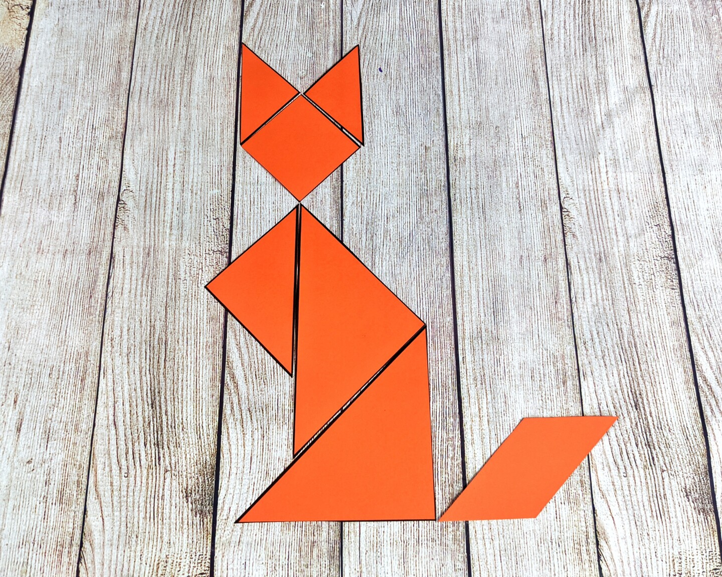 A tangram is arranged in the shape of a cat.