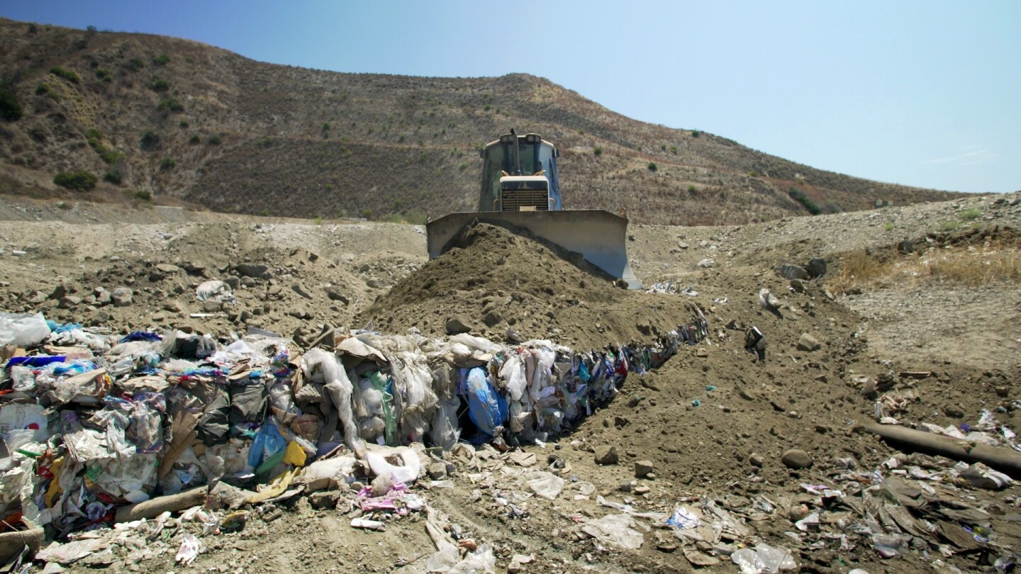 """Dirt being pushed over trash by tractor in a landfill   Still from """"Life in Plastic: California's Recycling Woes"""""""