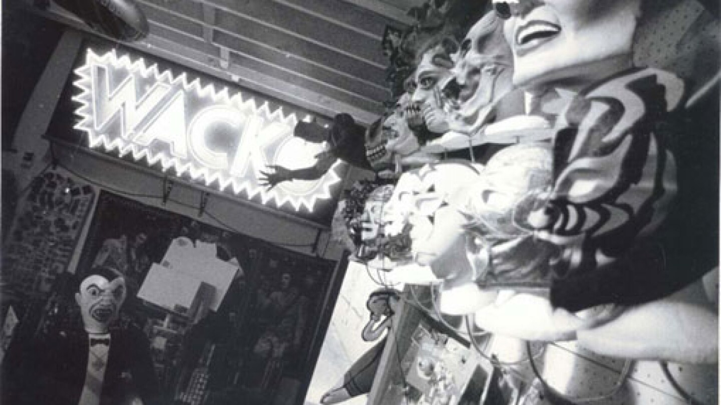 """A neon sign that reads """"WACKO"""" and walls covered with face masks adorn the interior of the store."""