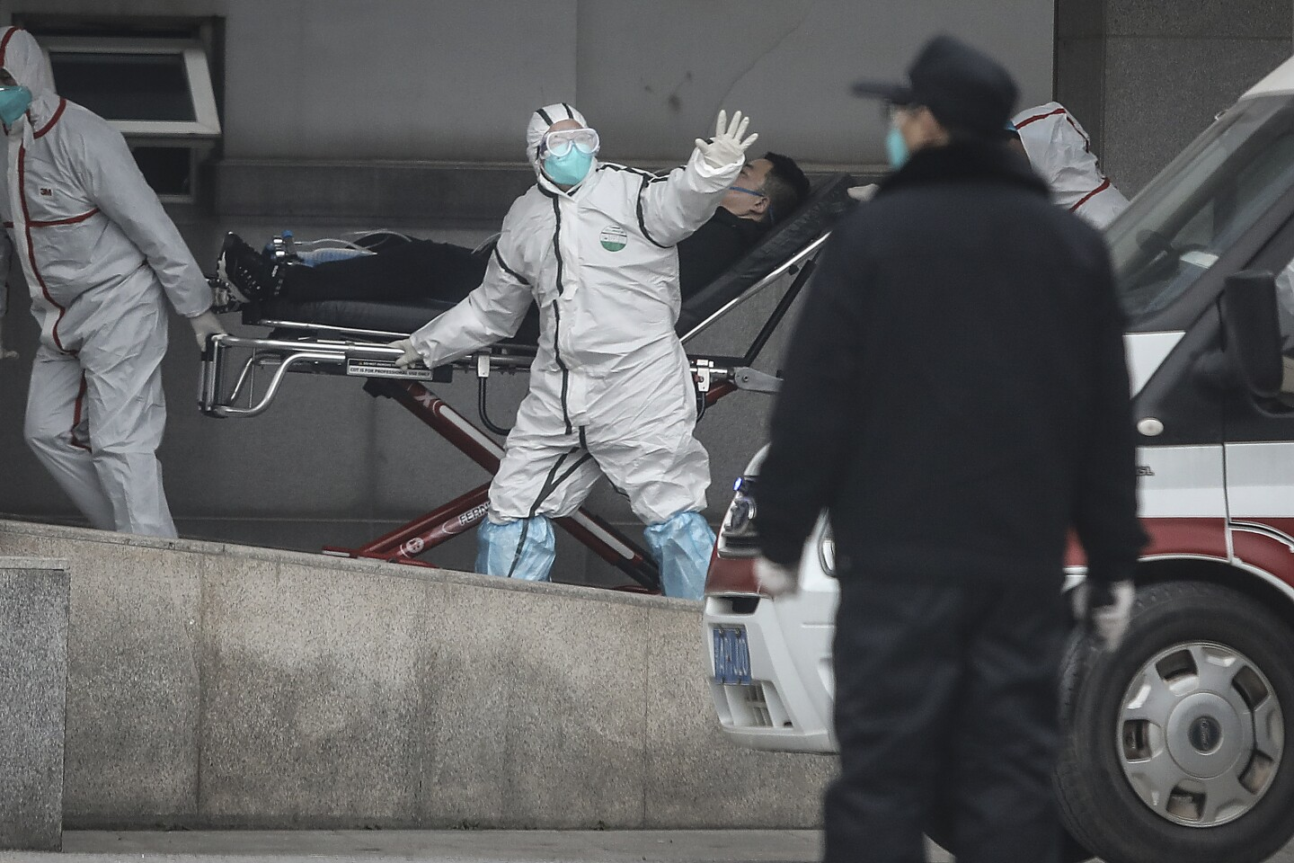 Two medical workers in white personal protective gear wave as they wheel a face mask-wearing man in a stretcher.