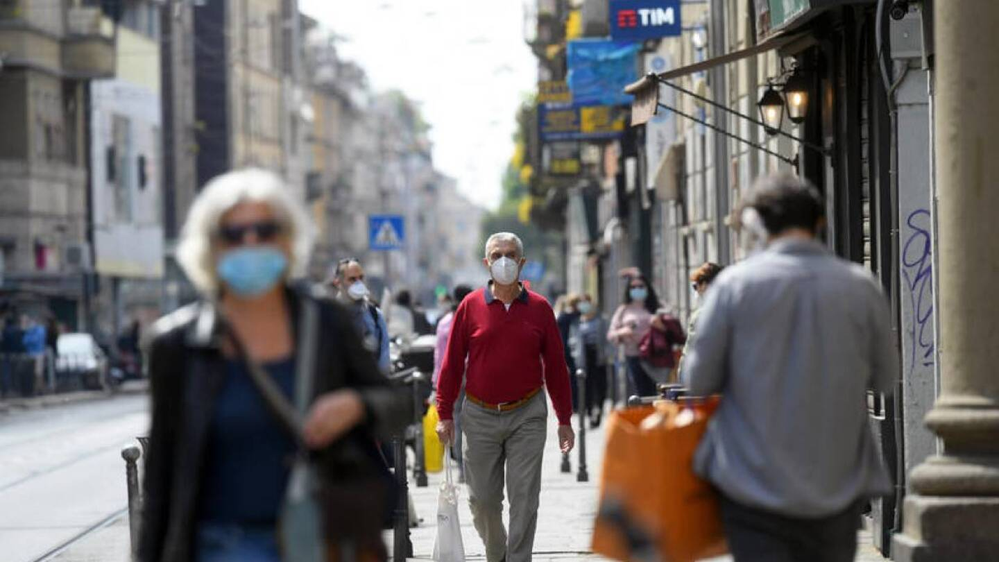People wearing protective masks walk in an increasingly busy street, amid the coronavirus disease (COVID-19) outbreak, in Milan, Italy April 18, 2020. | REUTERS/Daniele Mascol