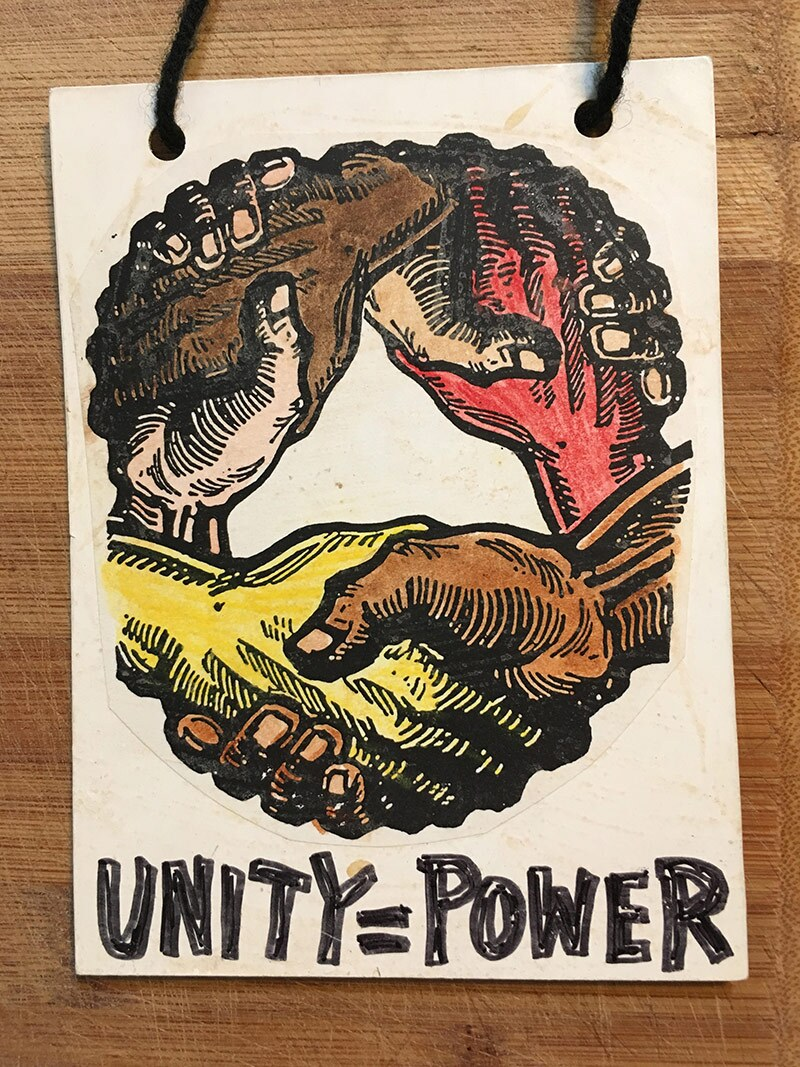 "A mat board necklace with a circle of multicolored hands holding each other that reads ""Unity=Power"""