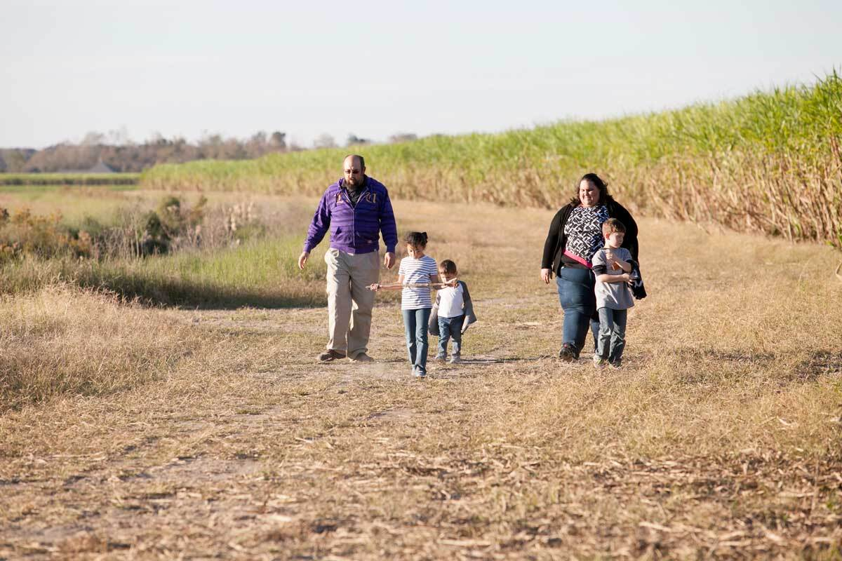 Chantelle Comardelle, the tribal executive secretary of the Biloxi-Chitimacha-Choctaw band, walks with her family on the site destined for the tribe's relocation. | Nicky Milne/Thomson Reuters Foundation