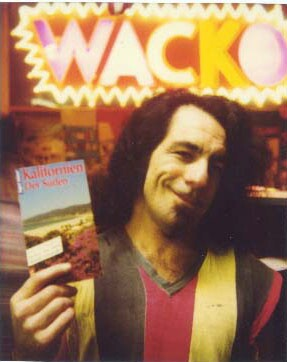"""Billy Shire inside WACKO, an extension to the Soap Plant. Behind him is a bright neon sign with the word """"WACKO"""" in vibrant letters. He's holding a brochure that reads, """"Kalifornien Der Soden."""""""