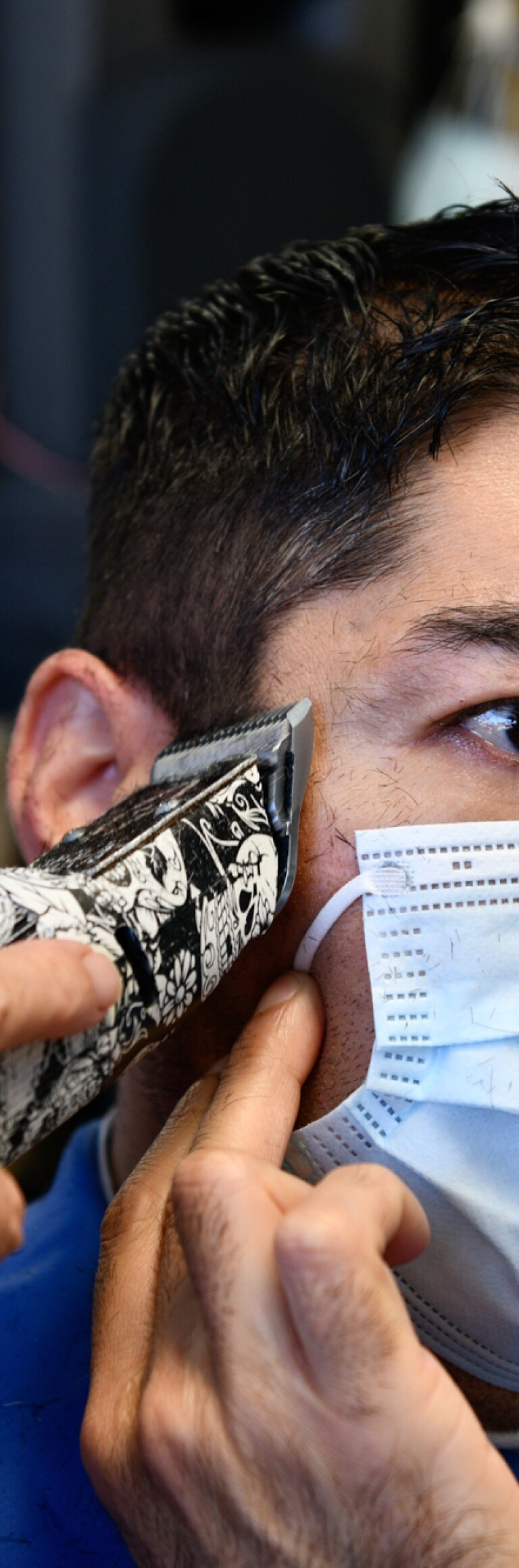 Carlos Hernandez holds his face mask while getting a haircut during the pandemic.