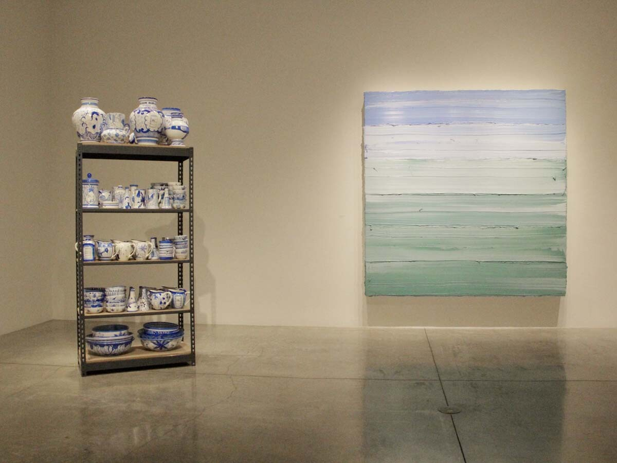"Eduardo Sarabia's ""History of the World (Consolidated) #2,"" 2008, ceramic on wood and steel shelving various sizes; overall dimensions installed: 102 1/2 x 36 1/2 x 22 1/2 in. Jason Martin ""Untitled (Mixed White/ Emerald Green/ Royal Blue Deep) I ,"" 2018."