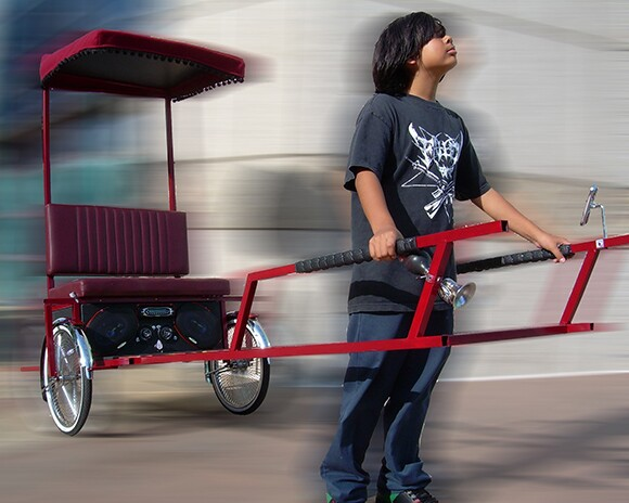 A little boy carries a rickshaw crossed with a lowrider, an art piece created by Clement Hanami.