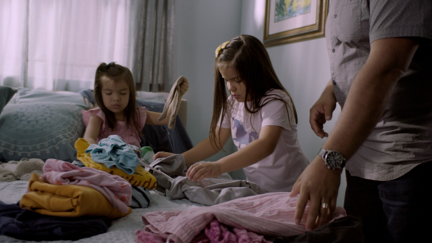 A family is doing laundry together to demonstrate how you can practice sorting and collecting at home.