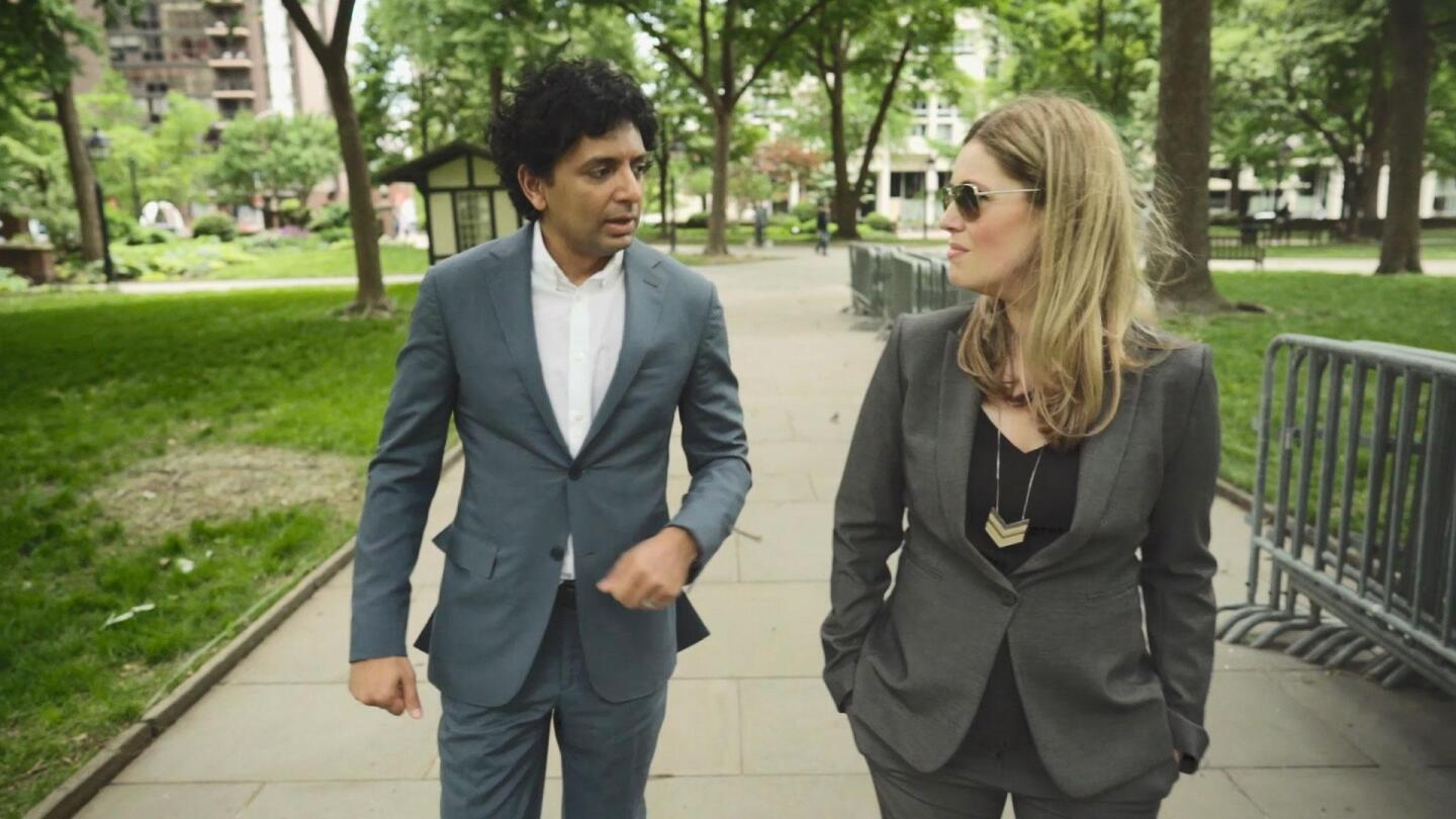 """Kate Sullivan and M. Night Shyamalan stroll through a park in """"To Dine for with Kate Sullivan."""""""