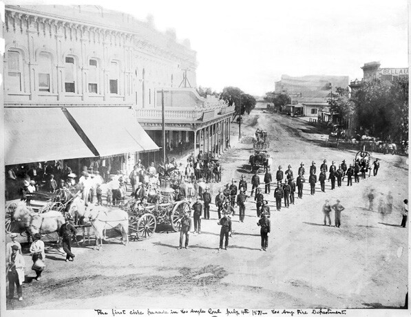 In what the caption describes as the first civic parade in Los Angeles, the L.A. Fire Department marches down Main Street on July 4, 1871.  Courtesy of the Title Insurance and Trust / C.C. Pierce Photography Collection, USC Libraries.