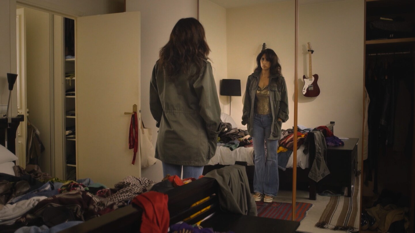 "Still From Border Blaster 505, ""Until Later:"" A young woman stands in front of a mirror in a bedroom."