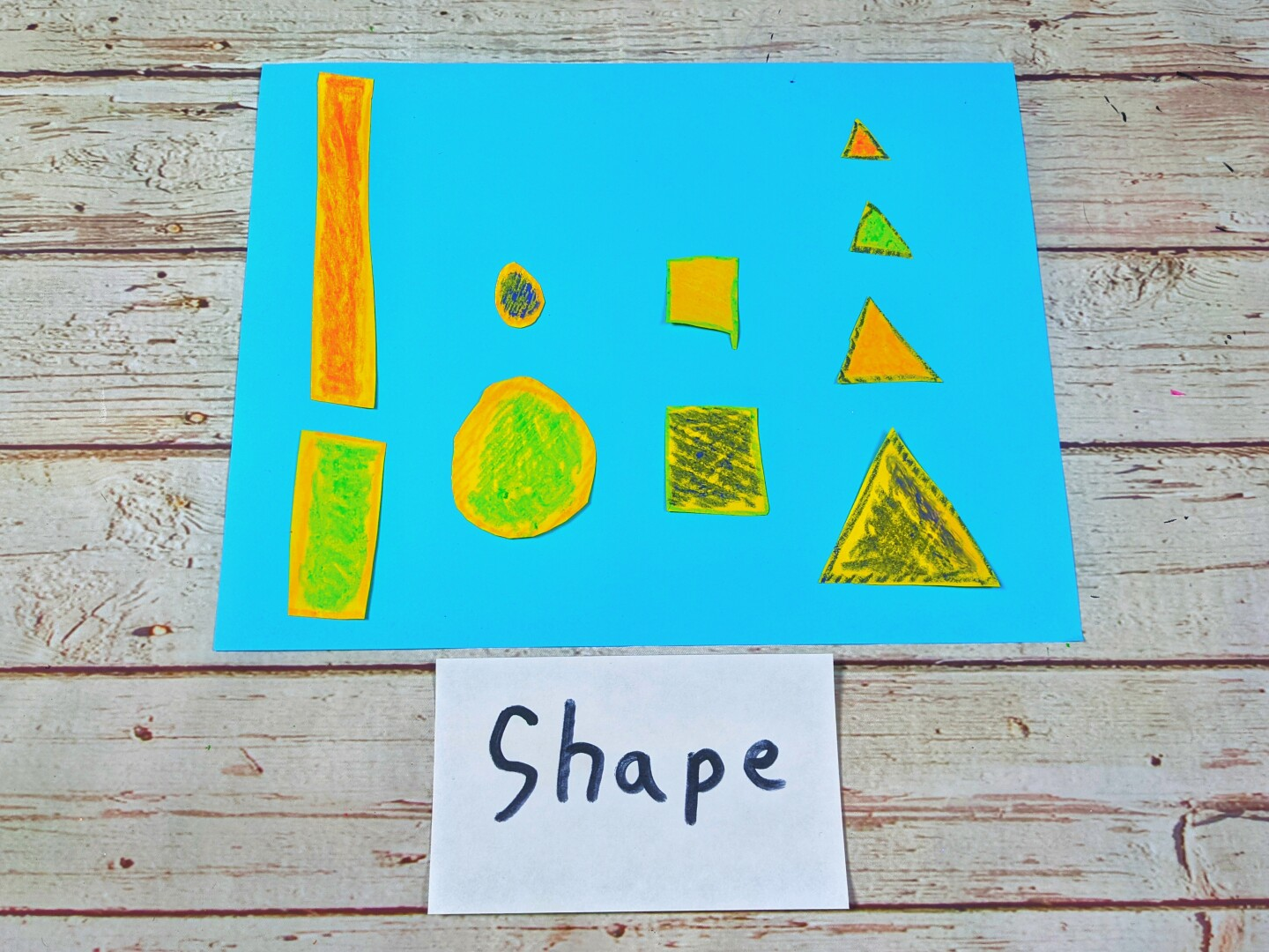 "A blue sheet of paper with colorful shapes on top of it. An index card with the word ""Shape"" on it is below it."