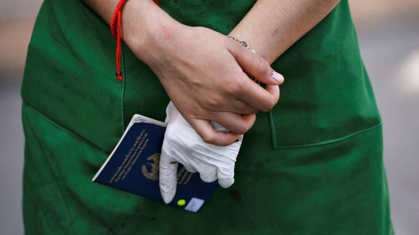 Close up shot of a woman's hands, one wearing a white latex glove, as she holds a passport.