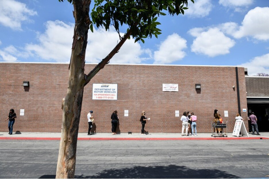 People stand in line while social distancing for the Department of Motor Vehicles.