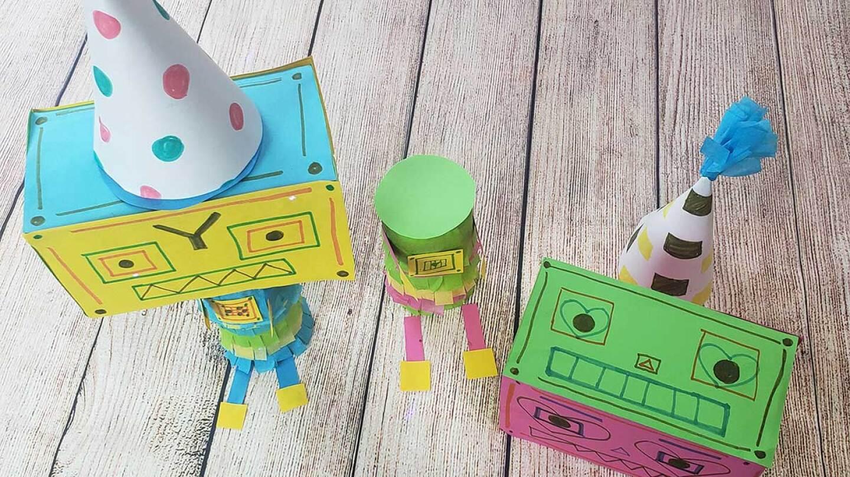 Sobre una mesa se colocan dos robots de cartón coloridos y papel de construcción.