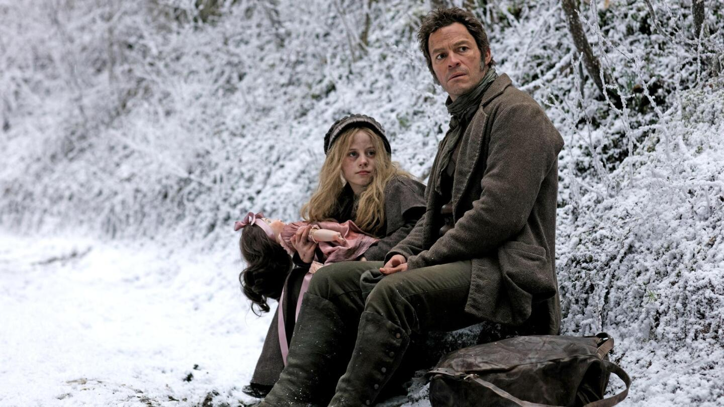 "Jean Valjean and Cosette sit together in a snowy part of the woods. | Still from ""Les Miserables On Masterpiece"""